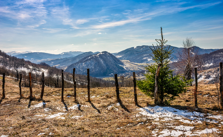 suburban neighborhood: spring has sprung in rural area. wooden fence on agricultural field, yellow weathered grass covered with snow. snowy peaks of mountain ridge in the distance. nature on sunny day under blue sky Stock Photo
