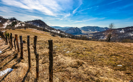 spring has sprung in rural area. wooden fence on agricultural field, yellow weathered grass covered with snow. village in the distance at the mountain ridge foot. nature on sunny day under blue sky