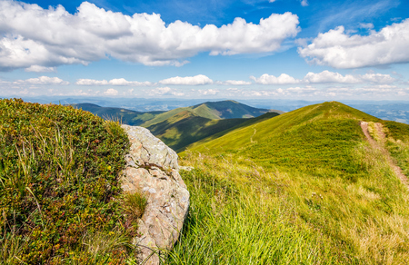 landscape with grassy meadow and giant boulders on the slope of a hill in Carpathian mountain ridge.  beautiful sunny summer day Stock Photo