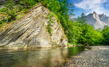 composite summer landscape with trees on a cliff nearthe shore of a clear river at the foot of epic High Tatra mountain ridge with rocky peaks under blue sky with clouds Stock Photo