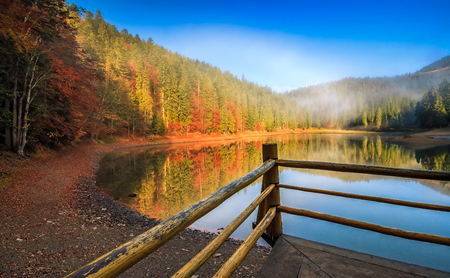 pier with wooden fence on the Lake in mountain. coniferous forest and some trees with red foliage at foggy sunrise in autumn Stock Photo - 75101966