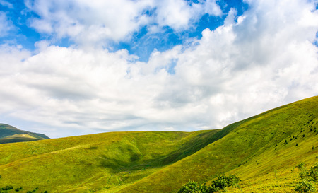 deep blue sky with some clouds over the green and grassy hills of Carpathian alps. road winds uphill the hillside meadow. beautiful minimalistic summer landscape in good day weather. Stock Photo