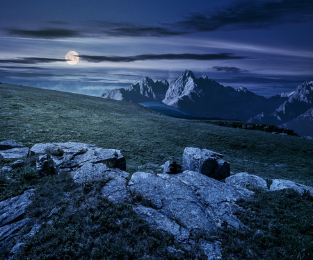 Composite night landscape with full moon. rocky peaks of mountain ridge and rocks on hillside under the dark sky with clouds and stars. picturesque fantasy view. Stock Photo