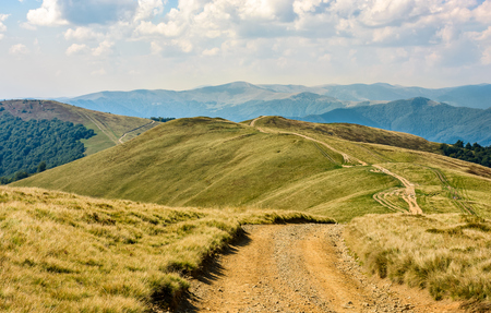 winding path through large meadows on the hillside. mountain ridge landscape in summer time Stock Photo