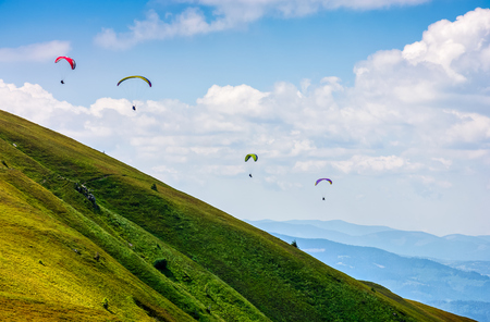 Skydivers fly over the mountains. Parachute extreme sport Stock Photo - 75784722