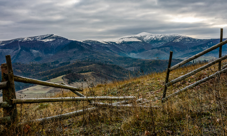 wooden fence on the hill with weathered grass. mountains with snowy peaks in the distance. Late autumn landscape in cloudy weather. Stock Photo