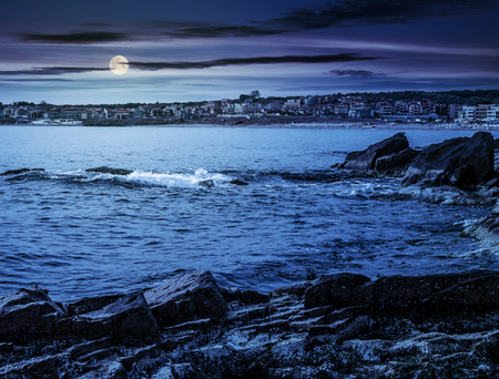 Rocky shore and sandy city beach in mellow season. Beautiful and warm weather on the coast of Black sea at night in full moon light