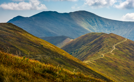 winding path through large meadows on the hillside of Carpathian mountain ridge