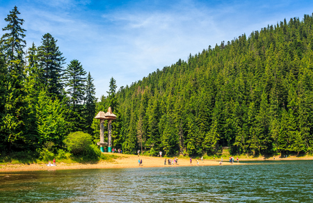 tourist visiting mountain lake among the green spruce forest in picturesque summer landscape. beautiful weather with blue sky and some clouds