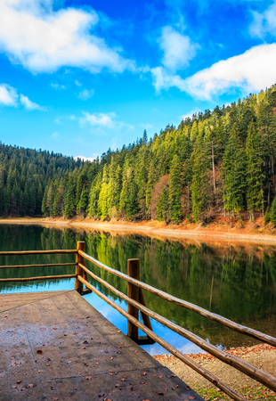 pier with wooden fence on the Lake in mountains. coniferous forest and some trees with red foliage in autumn. National Park Synevir, Ukraine