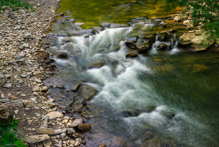 Rapid stream flow along shore covered with stone. beautiful nature view in summer time.