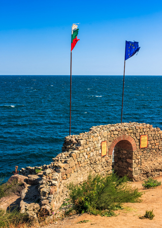 Northen tower with entrance to the fortress of sozopol. European and Bulgarian flag wave abow the Black Sea shore