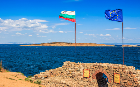Northen tower with entrance to the fortress of sozopol. European and Bulgarian flag wave abow the Black Sea shore. st Ivan and st Peter islands are seen in the distance