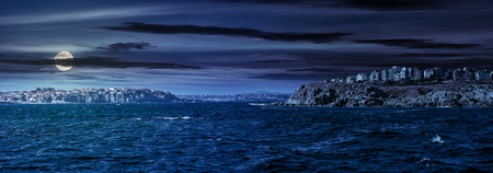 composite summer seascape. panoramic view of old resort town on a rocky cliff above the seashore. blue and calm water in the sea at night in full moon light