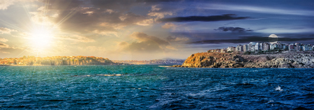 day and night time change concept. composite summer seascape. panoramic view of old resort town on a rocky cliff above the seashore. blue and calm water in the sea