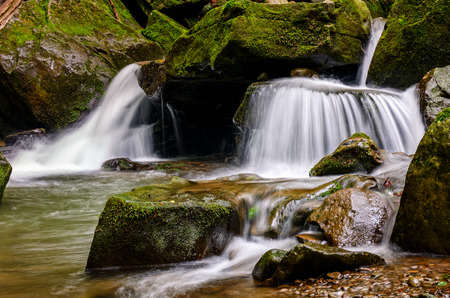 small cascades on the forest river among huge bouders covered with moss Stock Photo