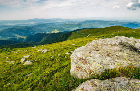 芝生の草原の美しいカルパティア山の尾根にある丘の斜面に巨大な岩と日当たりの良い夏の日のある風景します。 写真素材