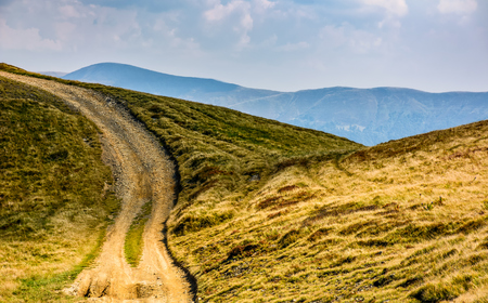 summer mountain landscape. path through the hill to the top. mountain ridge is seen in the distance Stock Photo
