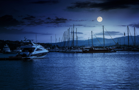 yacht at the pier of the old city  at night in full moon light Stock Photo