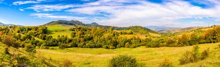 初期の秋山の風景。カルパティア山脈の中腹の森の近くの緑の草原のパノラマ風景。 写真素材