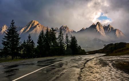 Reisbestemming concept afbeelding. Samengesteld landschap van Hoge Tatra-bergrand. Curve asfaltweg door vuren bos. Pieken verlicht door de zon in stormachtig weer met dramatische hemel.