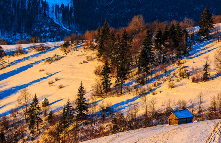 woodshed on snowy rural fields near forest. colorful sunrise in Carpathian mountains. Stock Photo