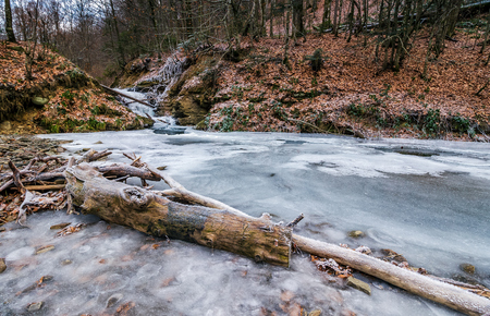 frozen waterfall on the  river among forest. old brown foliage on the ground Stock Photo