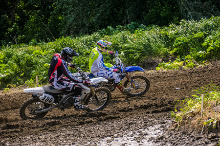 Extreme enduro MOTO SPORT. COUNTRY CROSS KTM racers turn on a corner in dirt. TransCarpathian regional Motocross Championship