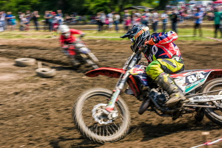 MX rider turns on a corner. Motion blur with flying dirt. TransCarpathian regional Motocross Championship