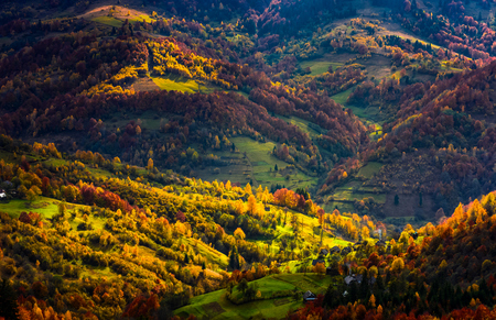 village in sunlit valley view from above. forest with golden foliage on hills. beautiful autumn evening Stock Photo