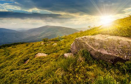 boulder on the grassy hillside. beautiful mountain landscape at sunset