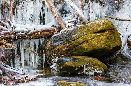 huge boulder in frozen waterfall