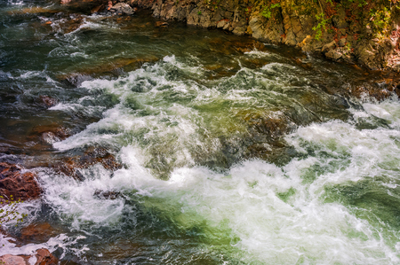 Rapid stream flow along shore covered with stone. beautiful nature background in summer time. Stock Photo