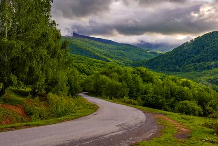 山の巻空アスファルト田舎道。曇りの日の出の美しいカルパティア風景