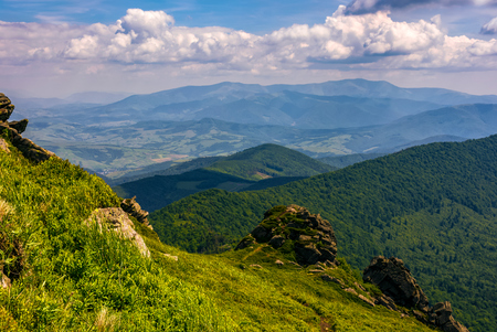 landscape with grassy meadow with giant boulders on the edge of a hill. Carpathian mountain ridge on a beautiful sunny summer day