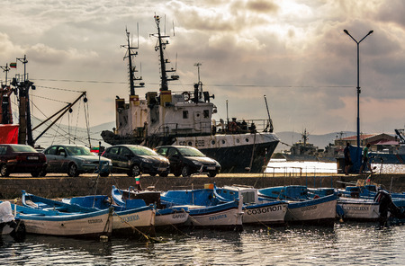 SOZOPOL, Bulgaria - AUGUST 19, 2015: rain in port of Sozopol at sunset. small fishing boats and few big one docked near pier with cars.