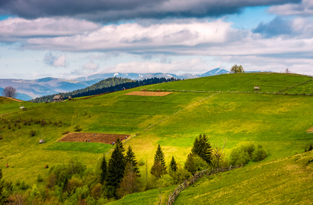 wooden fence on hillside in the rural area in mountains. beautiful Carpathian countryside landscape.