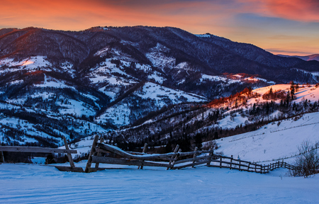 epic red sunrise in Carpathian countryside landscape. wooden fence through hillside with forest. Magical frosty morning.