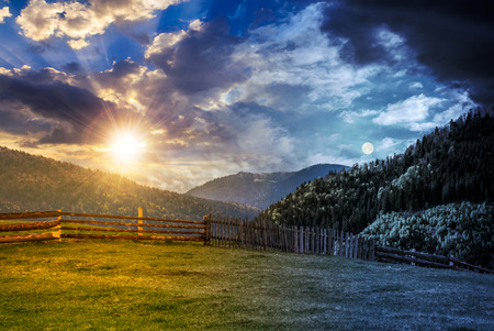 day and night time change concept. wooden fence through the grassy meadow in mountains. beautiful Carpathian countryside landscape with cloudy sky with sun and moon Stock Photo