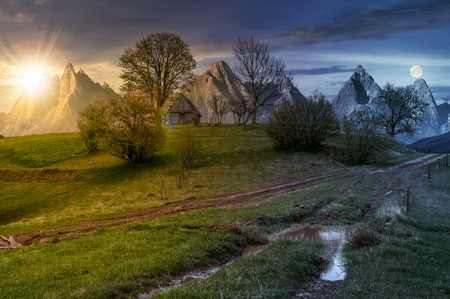 day and night time change concept; woodshed among trees on a hill by the road.  Composite High Tatras countryside landscape in dramatic weather with sun and moon Stock Photo