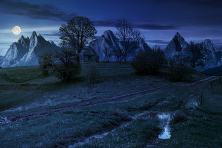 woodshed among trees on a hill by the road.  Composite High Tatras countryside landscape in dramatic weather at night in full moon light Stock Photo