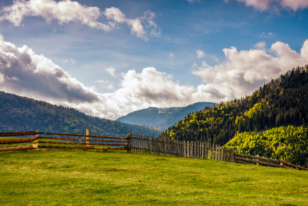 wooden fence through the grassy meadow in mountains. beautiful Carpathian countryside landscape with cloudy sky Stock Photo