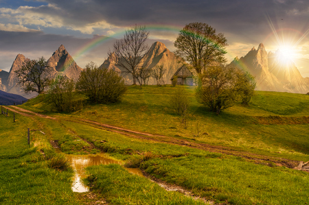 woodshed among trees on a hill by the road.  Composite High Tatras countryside landscape in dramatic weather at sunset with rainbow