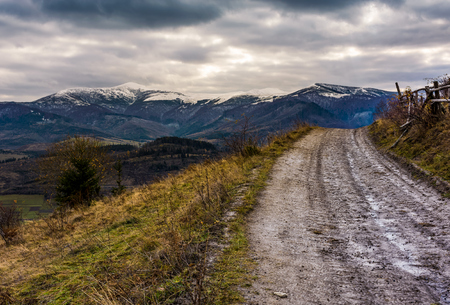 dirty countryside road to mountain ridge with snowy peaks. dramatic landscape with overcast sky Stock Photo