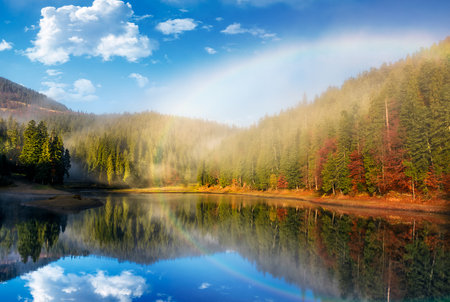 rainbow over the picturesque lake in foggy spruce forest. majestic autumn sunrise in gorgeous landscape with beautiful weather 版權商用圖片