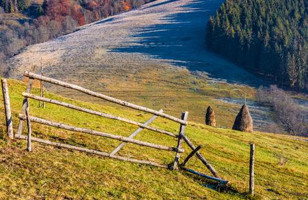 Hooiberg achter het hek op het landelijke veld op de heuvel. Ijzig gras in bosschaduw bij zonsopgang in de herfst