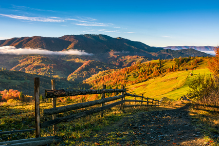 wooden fence by the road in rural area. autumn countryside landscape in mountains with grassy fields. beautiful misty sunrise
