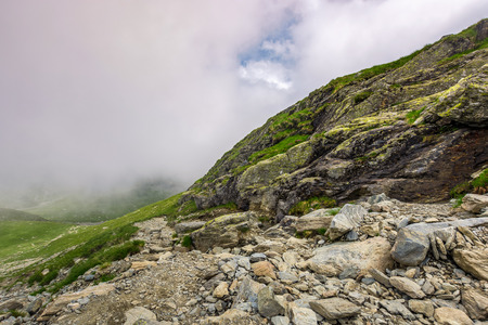 edge of steep slope on rocky hillside in foggy weather. dramatic scenery in mountains Banco de Imagens