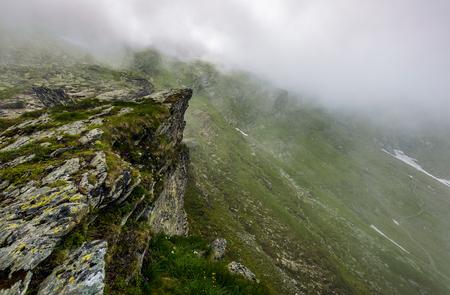 霧深い天候で岩が多い山腹の急斜面の端。山の劇的な風景