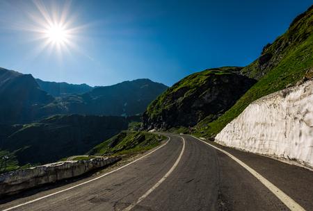山岳地帯にアスファルト道路上り坂。雪と太陽と澄んだ青い空の下で丘の中腹に草